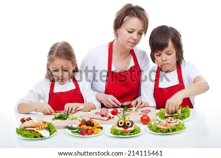 Kids and their mother preparing the party sandwiches - funny food creatures, isolated - stock photo