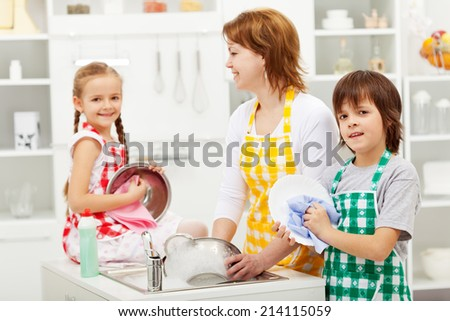 Kids and their mother washing dishes in the kitchen - stock photo