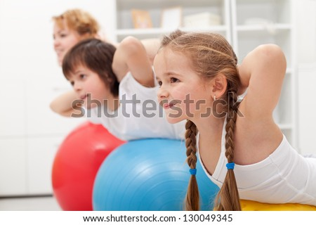 Kids and woman doing gymnastic exercises with balls - stretching their back - stock photo