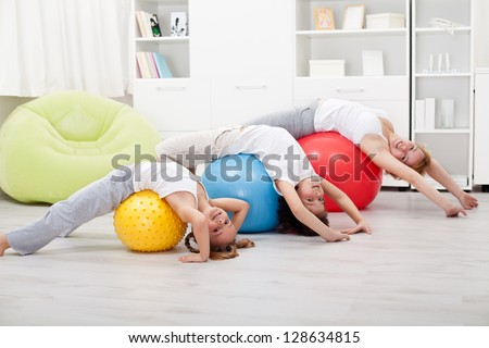Kids and woman doing stretching exercises - using large balls - stock photo