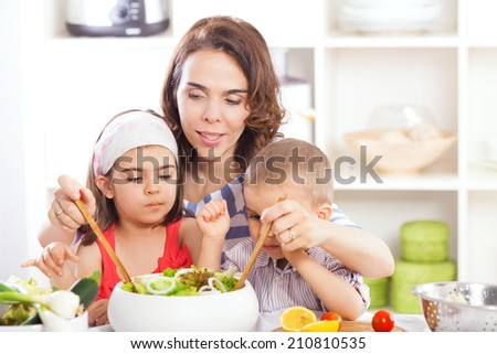 Kids are helping their mother to prepare salad - stock photo