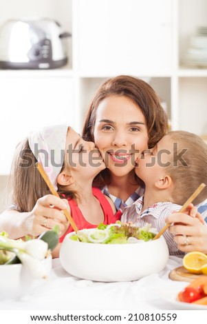 Kids are kissing mother in the kitchen before breakfast - stock photo