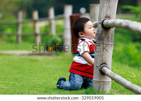 Kids are kneeling beside a wooden fence. - stock photo