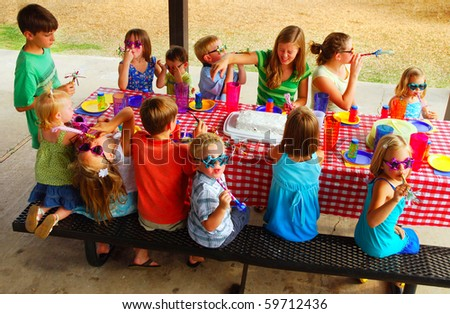 Kids at an outdoor birthday party and picnic - stock photo