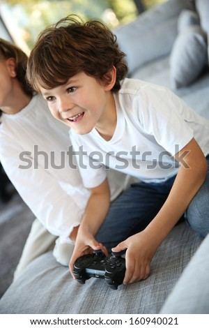 Kids at home playing video game - stock photo
