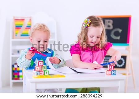Kids at preschool. Two children drawing and painting at kindergarten. Boy and girl happy to go back to school. Toddler kid and baby learn letters at child care. Class room with chalkboard and abacus - stock photo