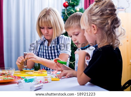 kids baking christmas cookies in front of christmas tree