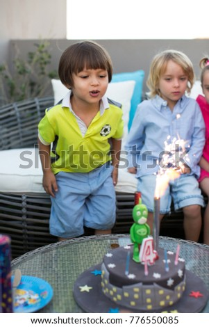 Kids birthday party. Child blowing out candles on colorful cake.