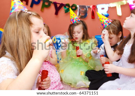 Kids blowing bubbles at the birthday party - stock photo