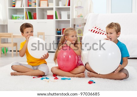 Kids blowing up large balloons indoors - stock photo