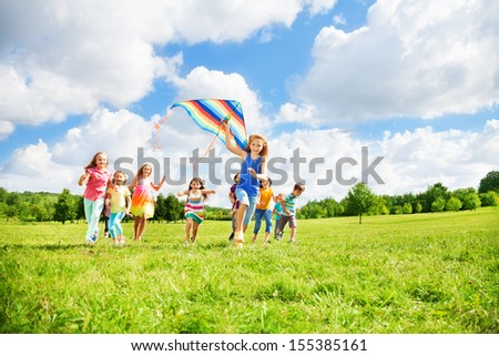 Kids boys and girls with kite running in the par on sunny summer day