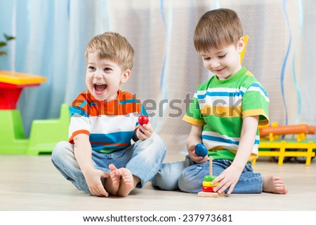 kids boys brothers with educational toy in playroom - stock photo