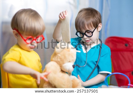 kids boys playing doctor with plush toy at home - stock photo