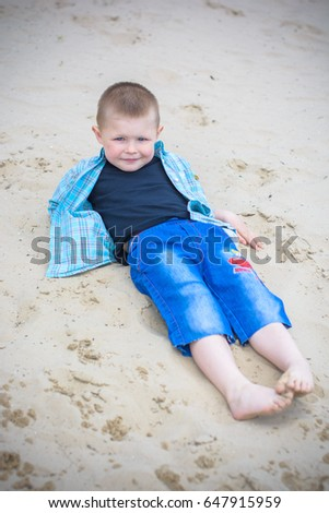 Kids boys playing on a beach near river with water and sand felling happy