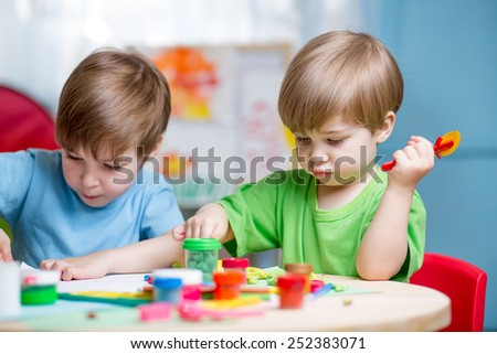 kids boys playing with plasticine at home - stock photo