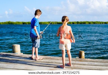 Kids brother and sister fishing together from wooden jetty - stock photo
