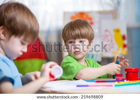 kids brothers hand making with play clay at home - stock photo