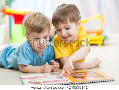 kids brothers reading a book at home or nursery - stock photo
