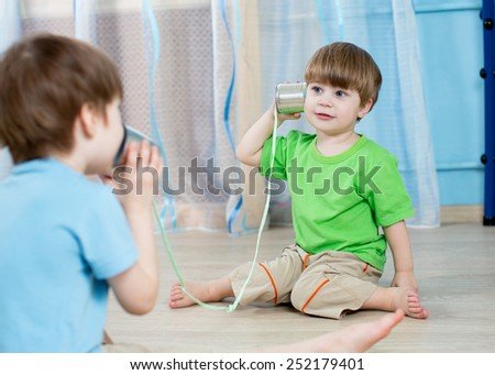 kids brothers talking with tin can telephone at home - stock photo