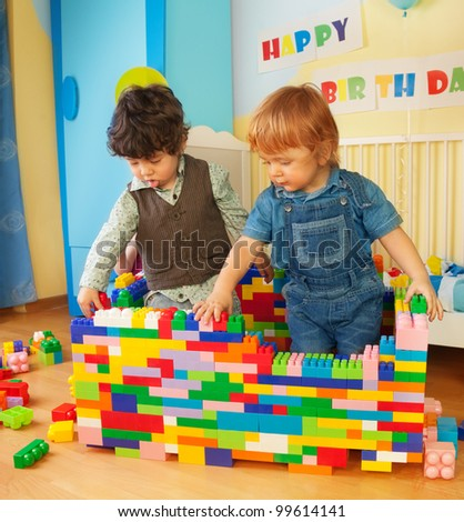 Kids building a wall of plastic blocks sitting in bedroom - stock photo