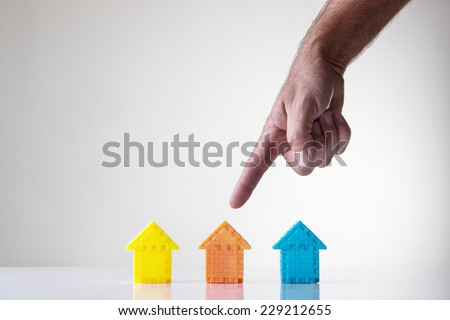 kids building blocks made into a shape of a house with a mans hand picking what house he wants - stock photo