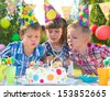 Kids celebrating birthday party and blowing candles on cake - stock photo