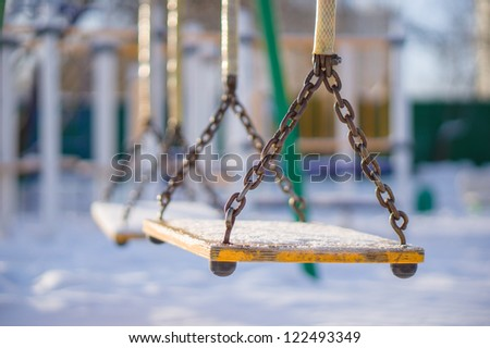 Kids chain swings on winter playground covered with snow - stock photo