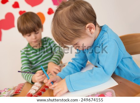 Kids, children, doing Valentine's day arts and crafts with hearts, pencils, paper, love concept