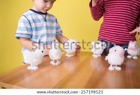 Kids, children having fun and playing with wound up easter bunny toys - stock photo