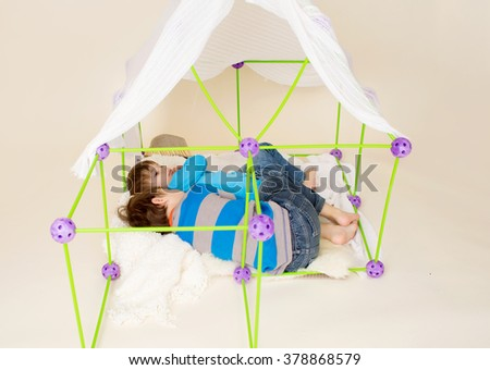 Kids, children, playing with a tent or fort made out of blankets, imagination, pretend play concept - stock photo