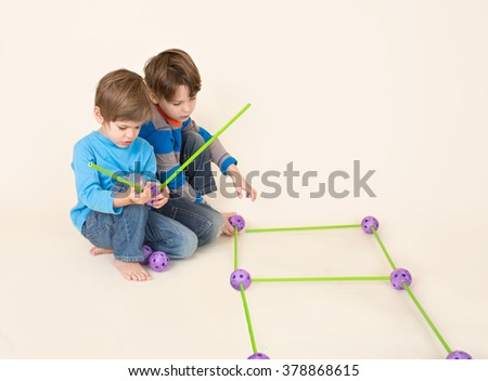 Kids, children, sharing construction or engineering set pieces