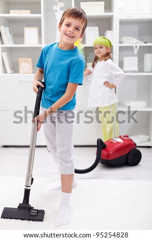 Kids cleaning the room - boy using a vacuum cleaner