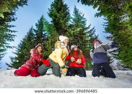 Kids competes in throwing snowballs at winter wood - stock photo