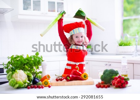 Kids cooking fresh vegetable salad in white kitchen. Children cook vegetables for vegetarian lunch. Toddler in chef hat eats healthy dinner. Little girl preparing and eating raw meal. Child nutrition. - stock photo