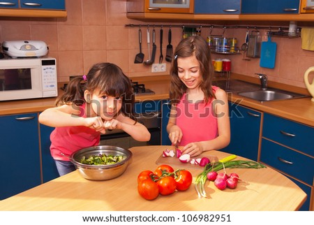 Kids cooking salad at kitchen. Happy smiling children cook healthy food together at home. Little girls preparing salad - stock photo
