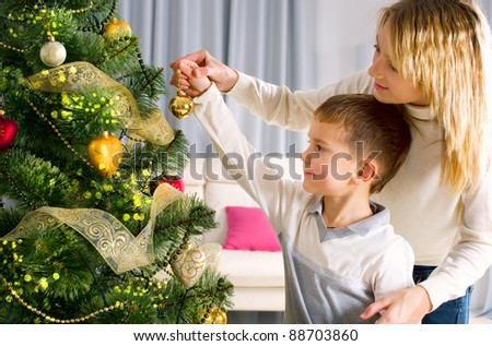 Kids decorating a Christmas tree with baubles in the living-room - stock photo