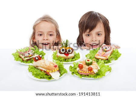Kids discovering the the healthy sandwich alternative - creative food creatures on plates - stock photo