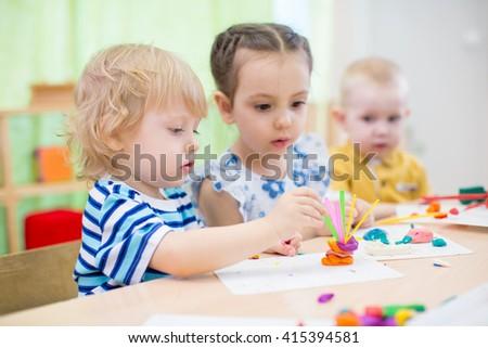 kids doing arts and crafts in kindergarten - stock photo