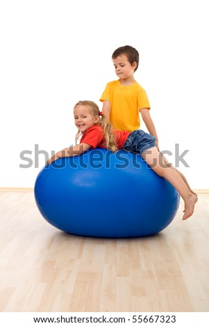 Kids doing exercises and having fun on large rubber ball - isolated