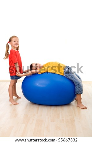 Kids doing gymnastic exercises with a large rubber ball having fun together - isolated - stock photo