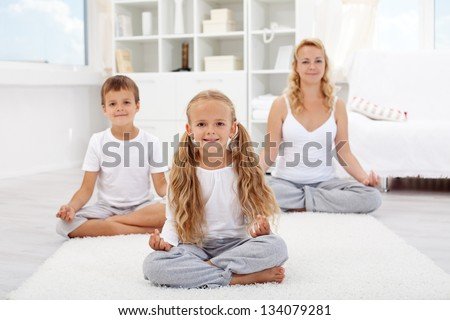 Kids doing yoga relaxing exercise with their mother at home - stock photo