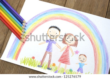 kids drawing happy family picture on the wooden table - stock photo