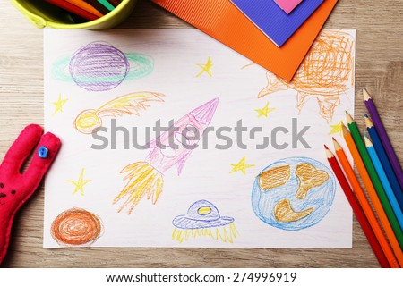 Kids drawing on white sheet of paper on wooden table, top view - stock photo