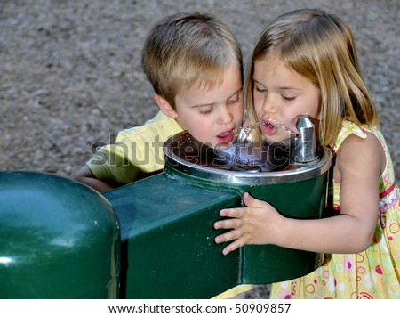 Kids drinking water from a public fountain - stock photo