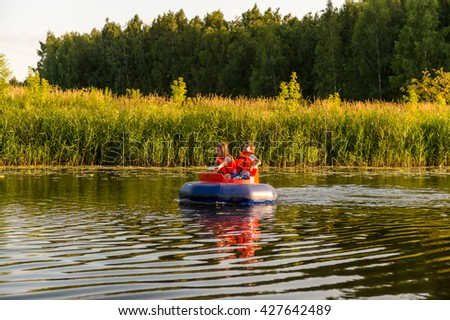 kids driving a blue rubber boat , kids having fun, children on holiday, brother and sister playing together,