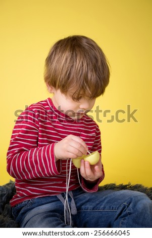 Kids easter activity and crafts: stringing plastic easter eggs for the egg hunt.  - stock photo