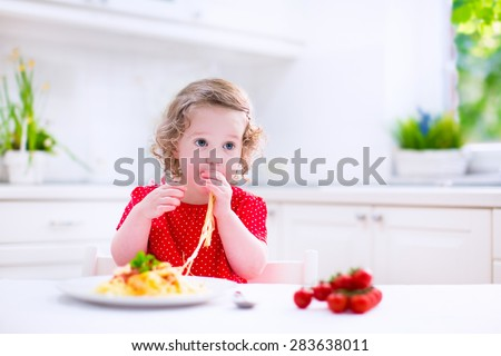 Kids eat pasta. Healthy lunch for children. Toddler kid eating spaghetti Bolognese in a white kitchen at home. Preschooler child cooking noodles with tomato and pepper for dinner. Food for family. - stock photo