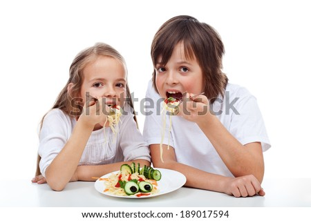 Kids eating a spaghetti dish with big appetite - isolated