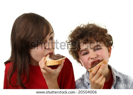 Kids eating bread with nut butter - stock photo