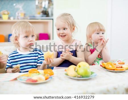 kids eating fruits in kindergarten dinning room - stock photo